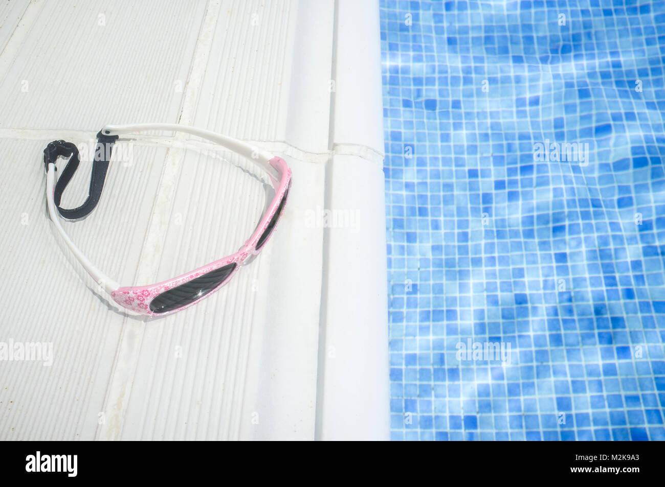 Little girl sunglasses over swimming poolside. Children summer concept - Stock Image