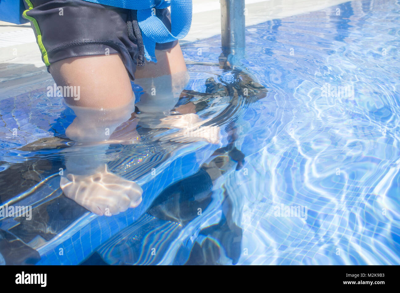Little boy steps down the swimming pool ladder with foot underwater. He wears a float belt - Stock Image