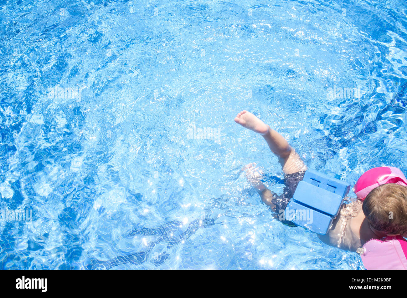 Little boy enjoying safety at swimming pool. He wears armband floats and float belt - Stock Image