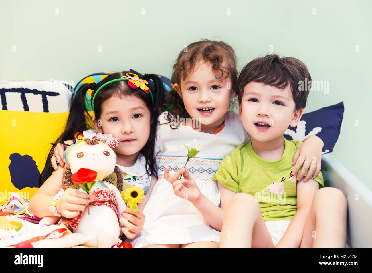 Happy children playing on the bed - Stock Image