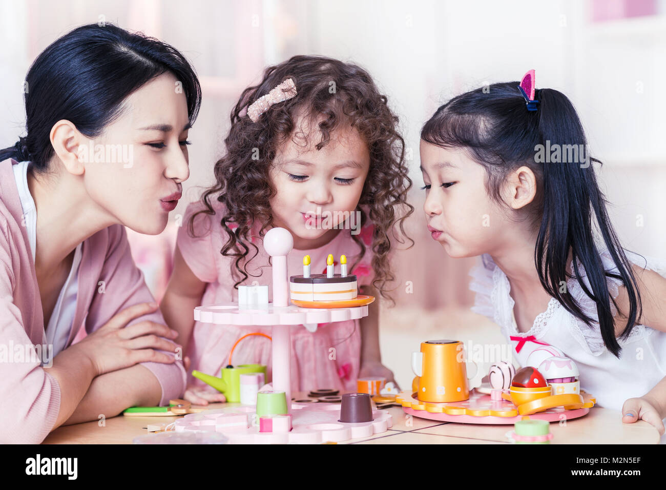 Two little girls to play with my mother in the bedroom - Stock Image