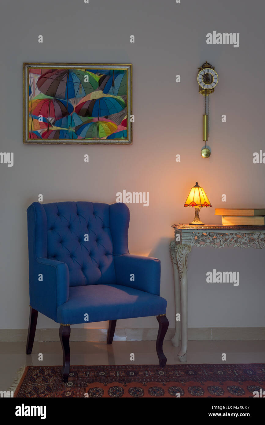 Vintage Furniture: Interior composition of blue armchair, vintage wooden beige table, illuminated table lamp, books, - Stock Image