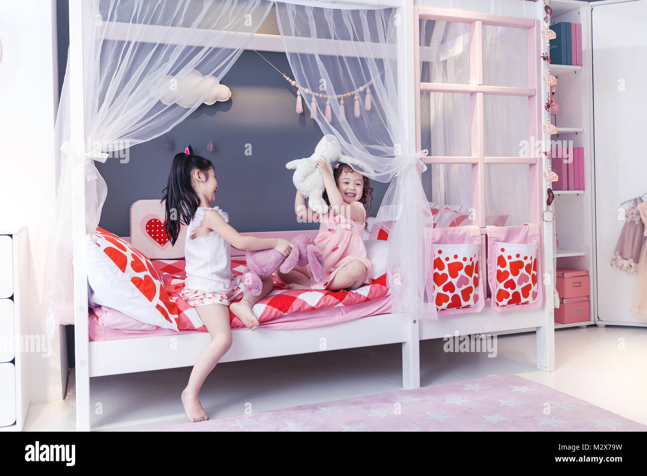 Playing cute girl on the bed - Stock Image