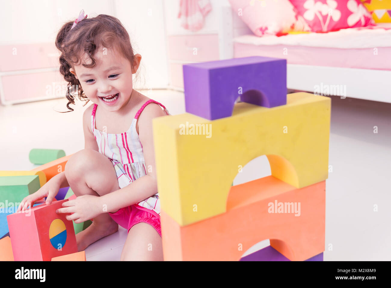 Cute little girl is playing with blocks - Stock Image