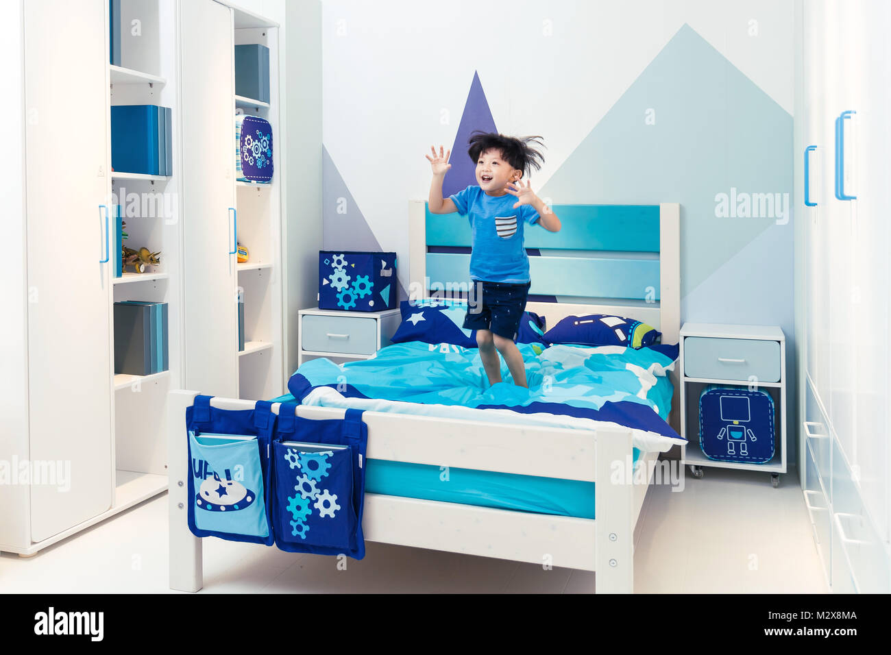 Lovely little boy playing on the bed - Stock Image