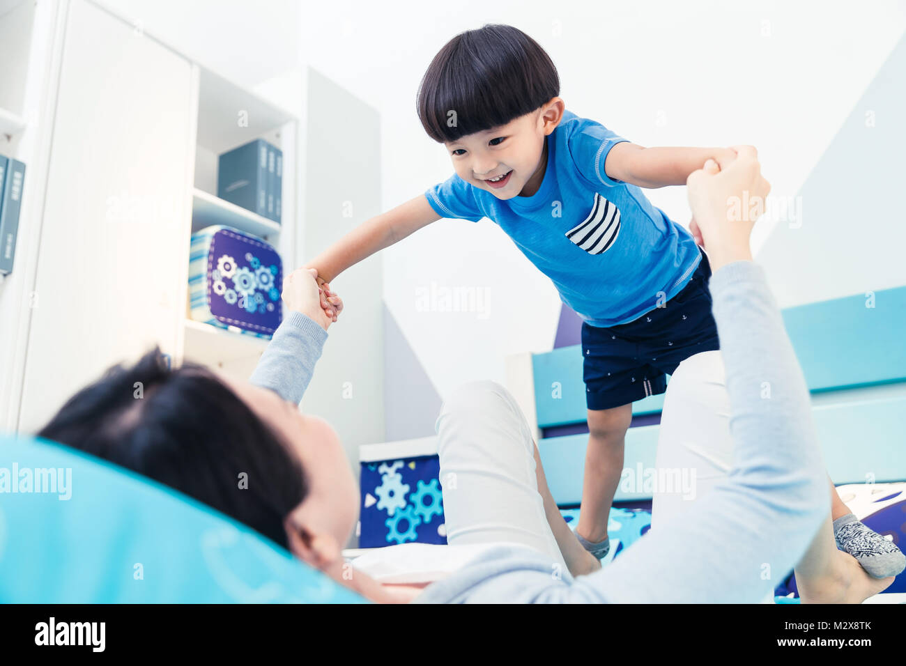 Lovely boy and mother play in the bedroom - Stock Image