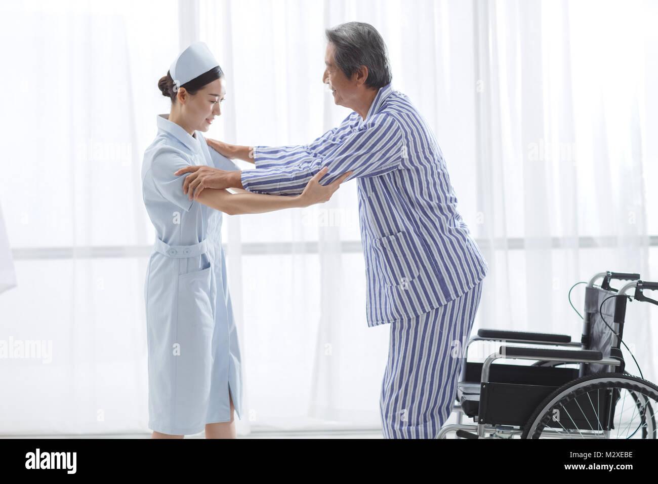 The nurse to assist the patient rehabilitation training - Stock Image