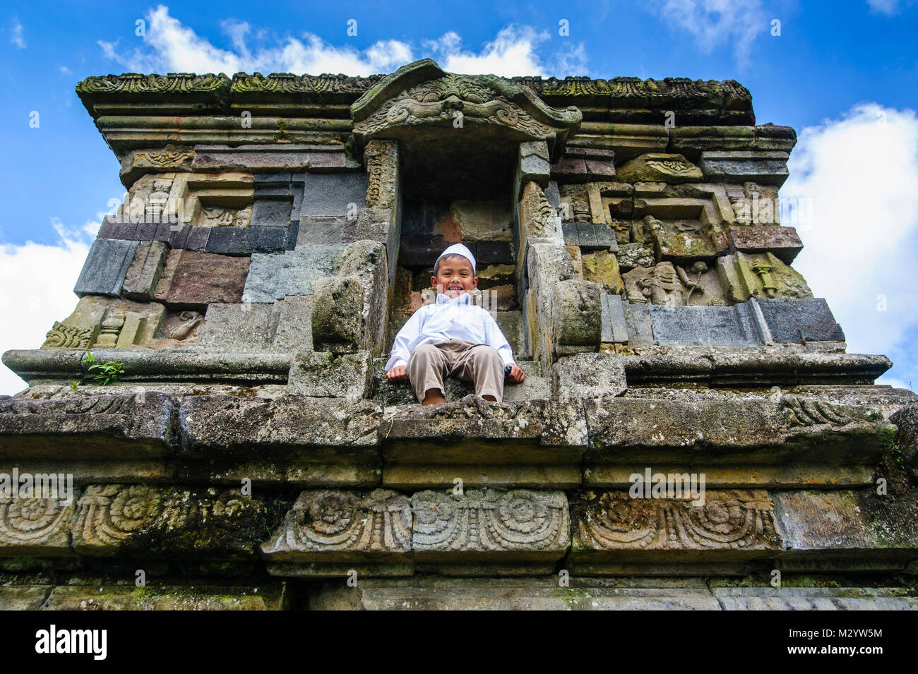 Young boy sitting in a temple of the Arjuna Hindu Dieng temple complex , Dieng Plateau, Java, Indonesia - Stock Image