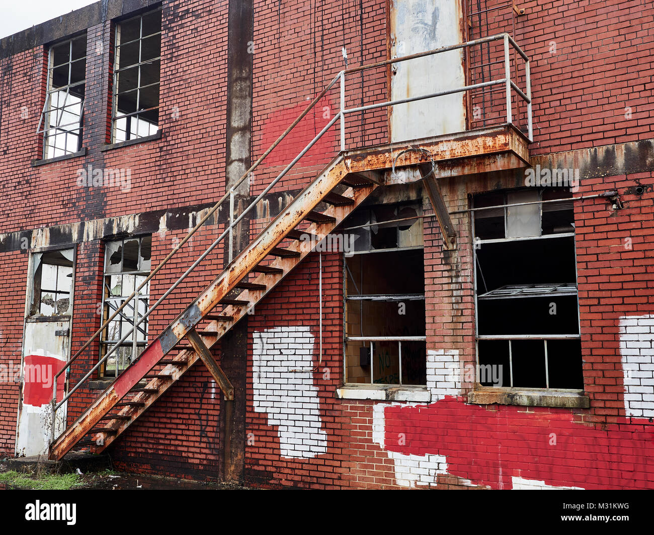 Second floor fire escape exterior of a run down abandoned building that is rusting and part of urban decay in Montgomery - Stock Image