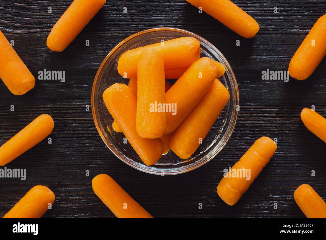 Bowl of Baby Carrots with Scattered Carrots on Dark Table - Stock Image