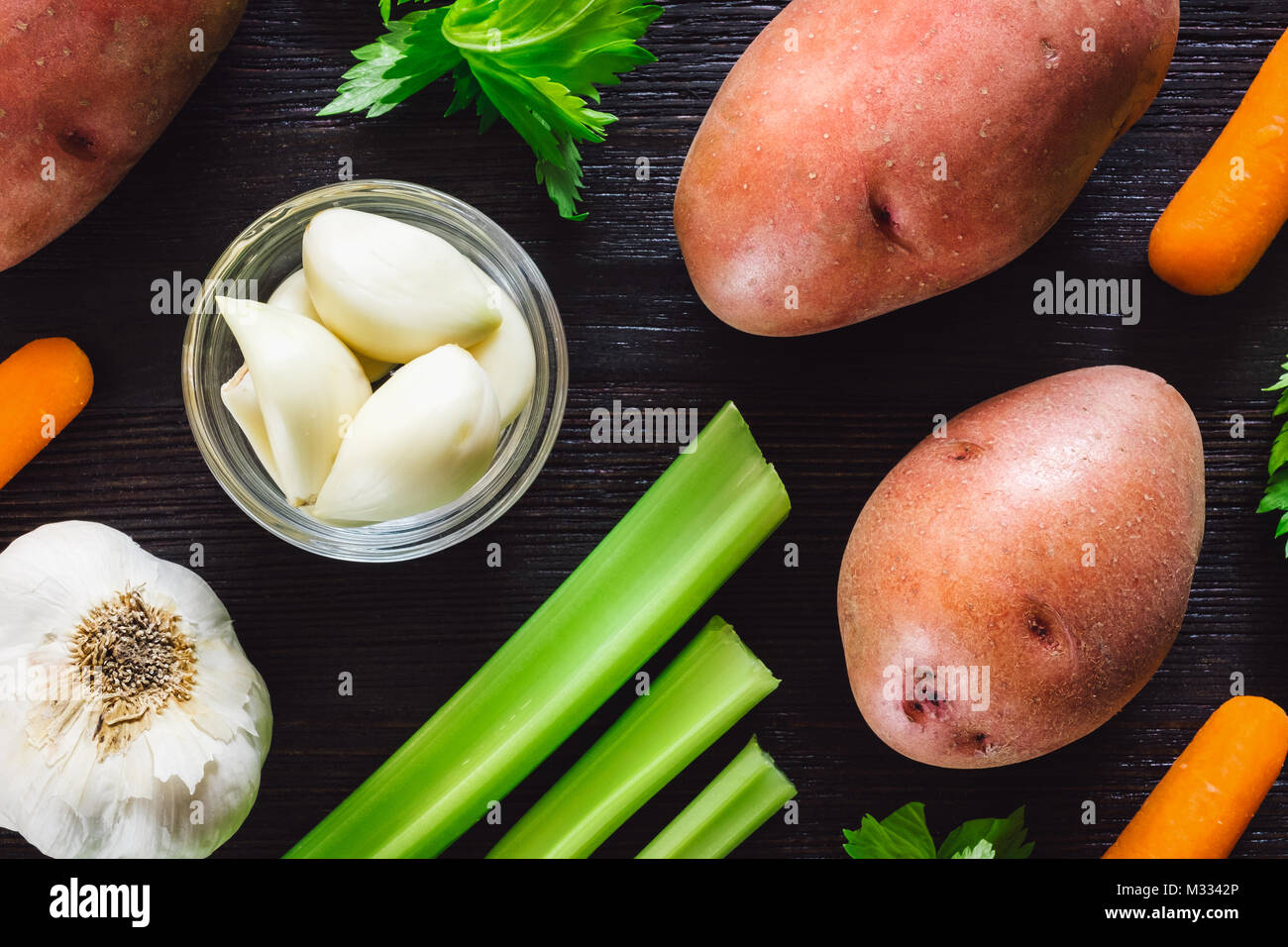 Mix of Vegetables Including Red Potatoes, Carrots, Garlic and Celery on Dark Background - Stock Image