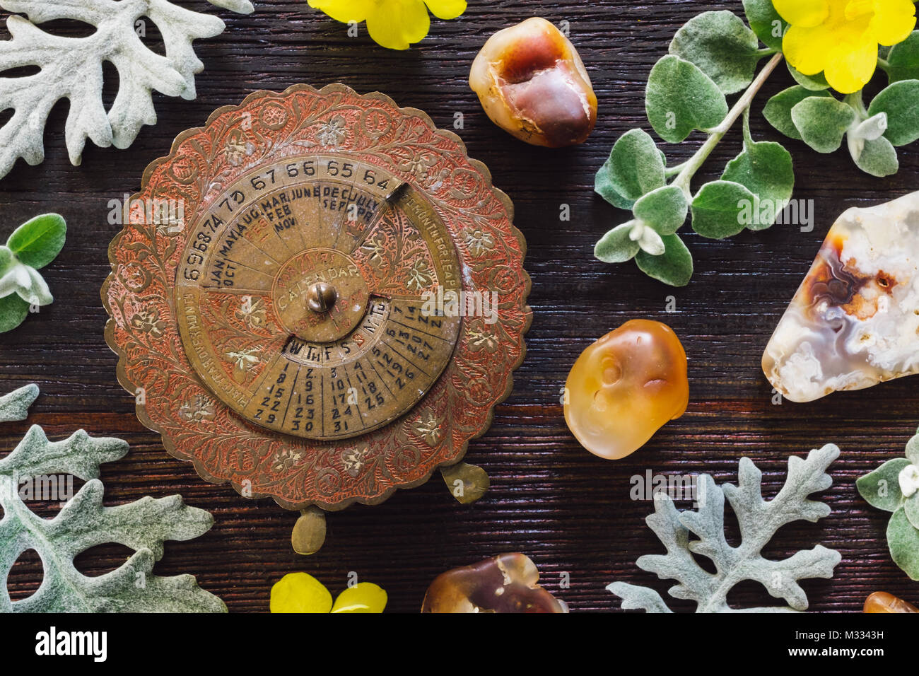 Brass Antique Calendar on Dark Table with Dusty Miller, Yellow Flowers and Fire Agate - Stock Image