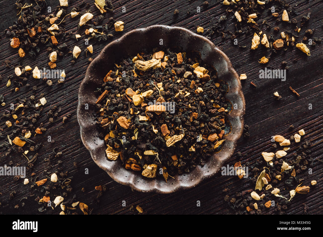 Ceramic Bowl of Masala Chai on Dark Wooden Table - Stock Image
