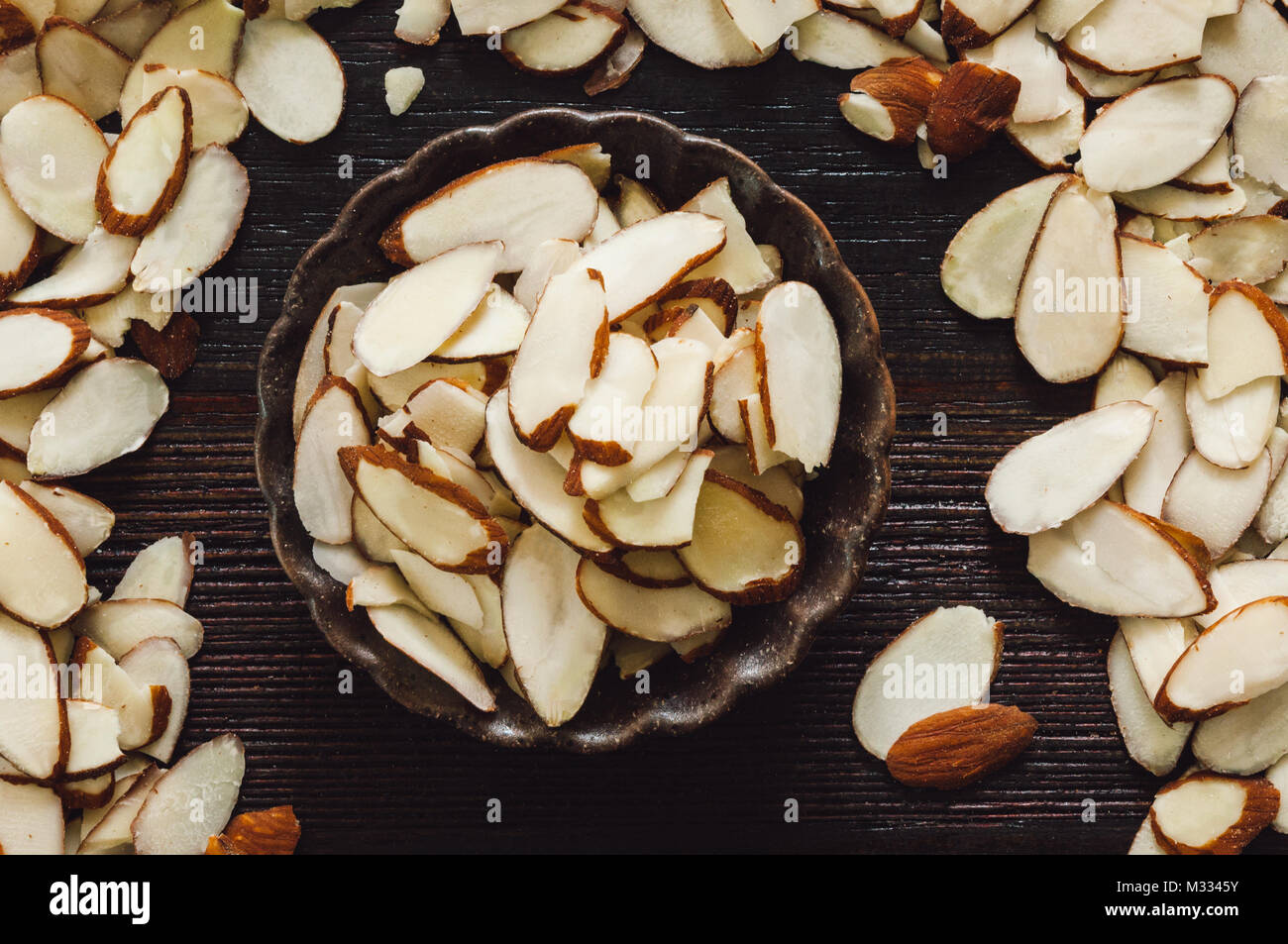 Sliced Raw Almonds Arranged on Dark Table - Stock Image