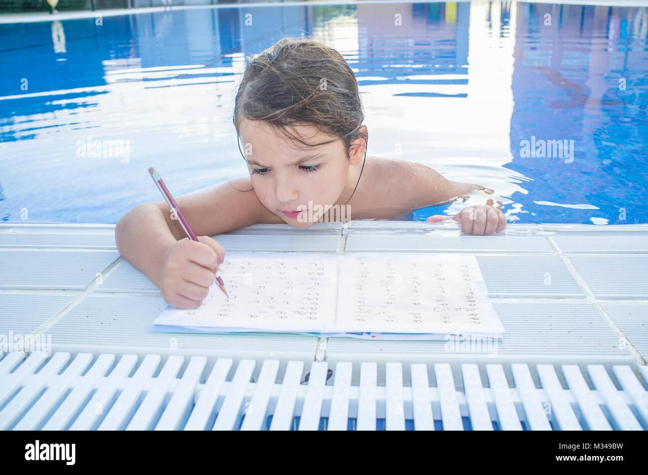 Child girl doing holidays homework over swimming poolside. Summer homework concept for children - Stock Image