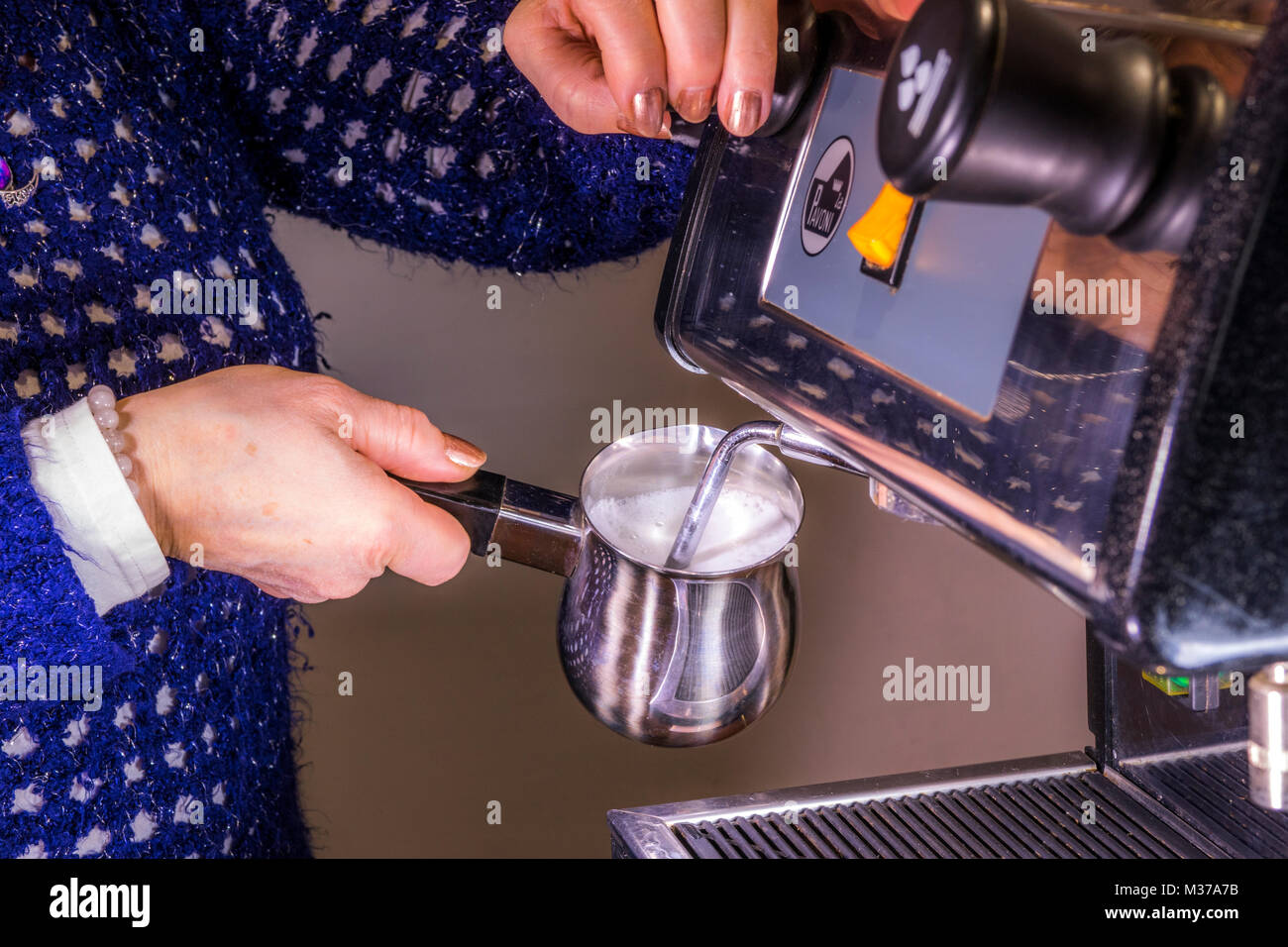 Woman's hand holding a stainless steel milk frothing jug, under the steam / steaming wand of a commercial espresso - Stock Image