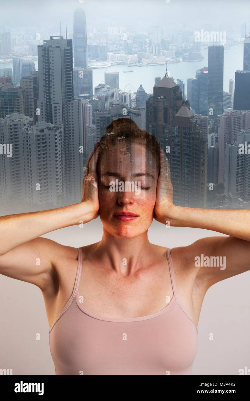MODEL RELEASED. Conceptual composite image of woman covering ears with eyes closed against backdrop of city. - Stock Image