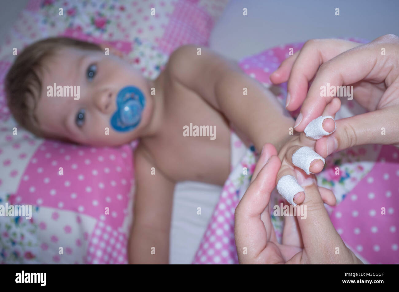 Baby boy shows his bandaged fingers before suffering a domestic accident. Domestic accidents concept - Stock Image