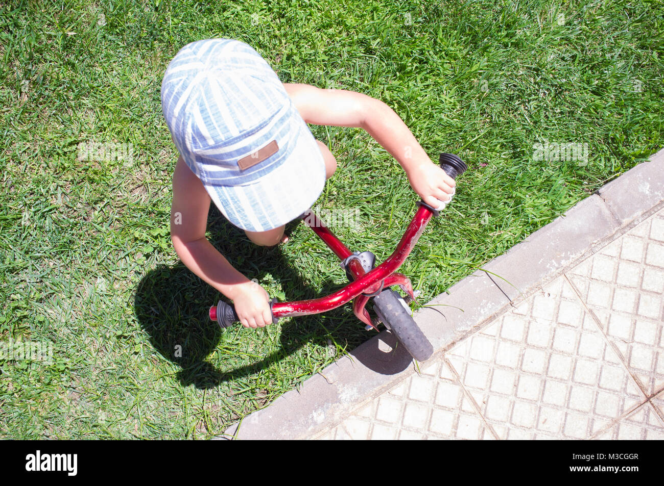 Boy in blue cap riding a blue balance bike (run bike). Happy child learning to keep balance in the garden - Stock Image
