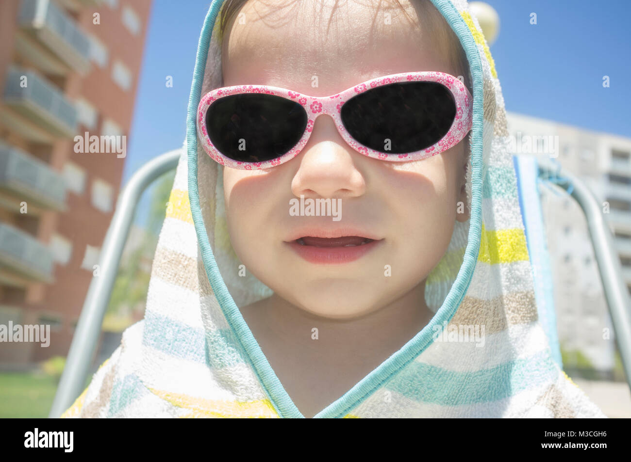 2 year baby boy with hooded poncho towel after swimming. He is sitting over beach chair - Stock Image