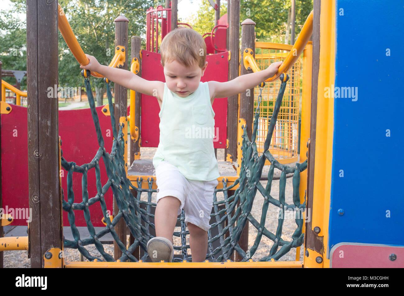 Toddler boy walking on blue net bridge. Equipment on a playground - Stock Image