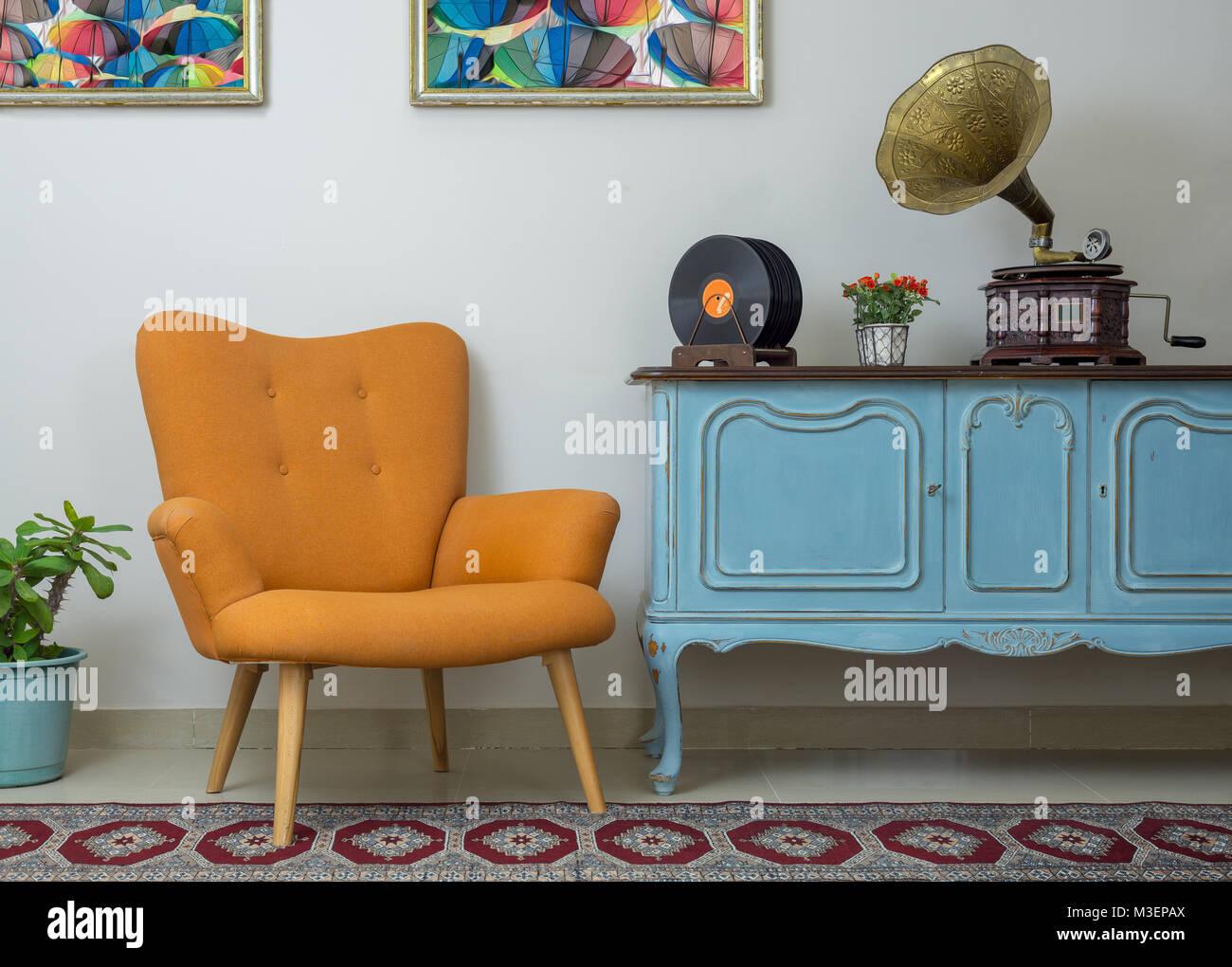 Vintage interior of retro orange armchair, vintage wooden light blue sideboard, old phonograph (gramophone), vinyl - Stock Image