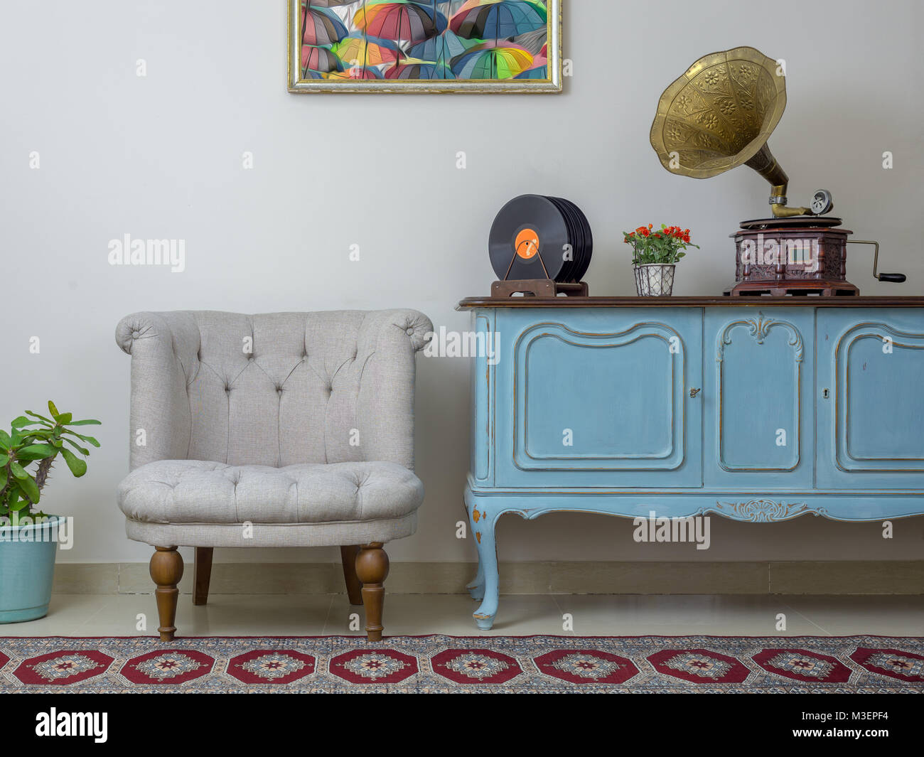 Vintage interior of retro off white armchair, vintage wooden light blue sideboard, old phonograph (gramophone) and - Stock Image