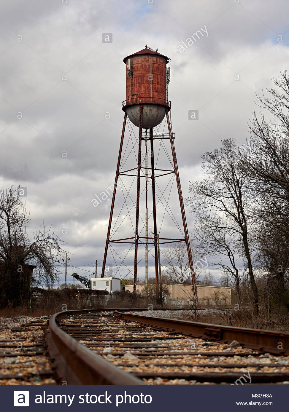 Old rusty or rusting water tower converted into a cell tower along railroad tracks in Montgomery Alabama, USA. - Stock Image