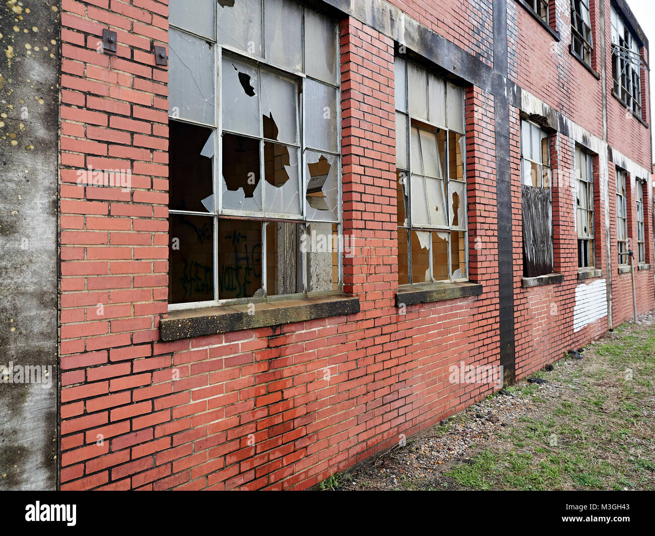 Exterior of abandoned brick building with broken windows in Montgomery Alabama, USA. - Stock Image