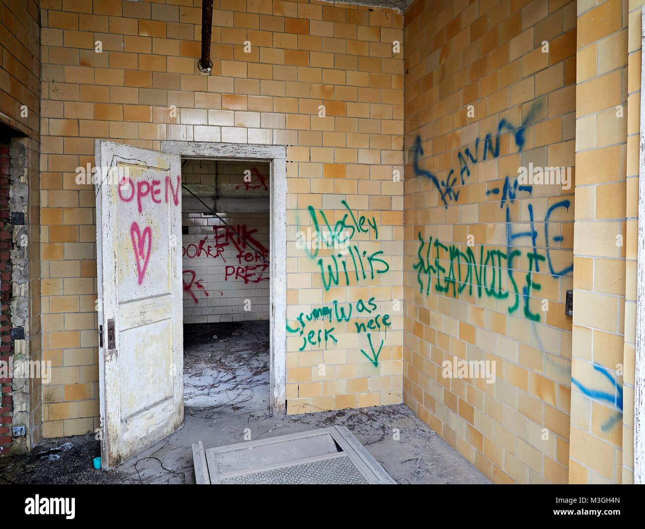 Interior of abandoned building with graffiti painted on the tile walls in an industrial section of Montgomery Alabama, - Stock Image