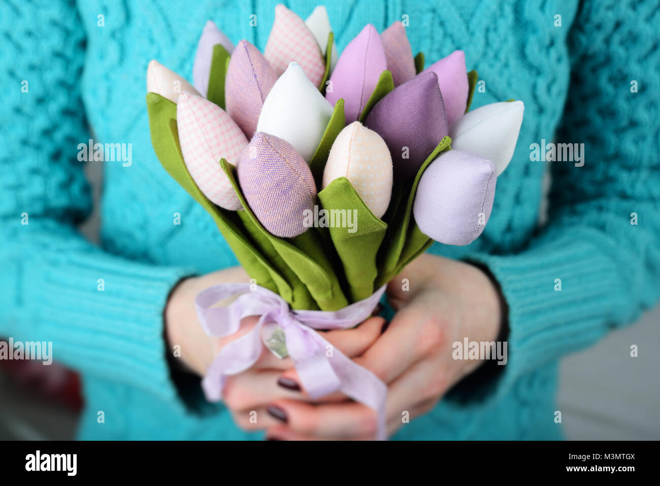 bouquet of beautiful toy tulips close-up in the hands of a girl in a blue knitted sweater. - Stock Image