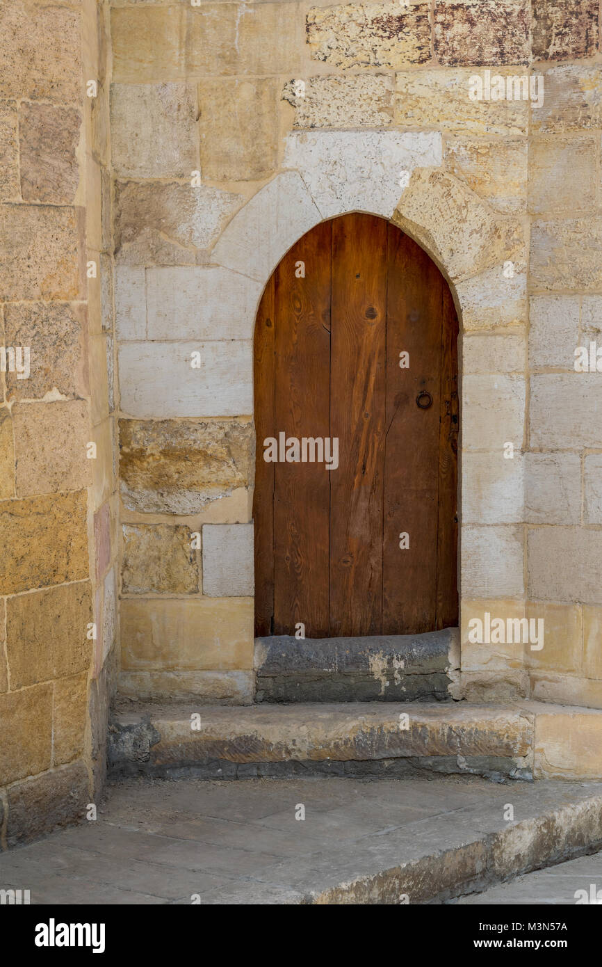 Grunge wooden aged vaulted door on exterior stone bricks wall of Amir Aqsunqur Mosque (Blue Mosque), Medieval Cairo, - Stock Image