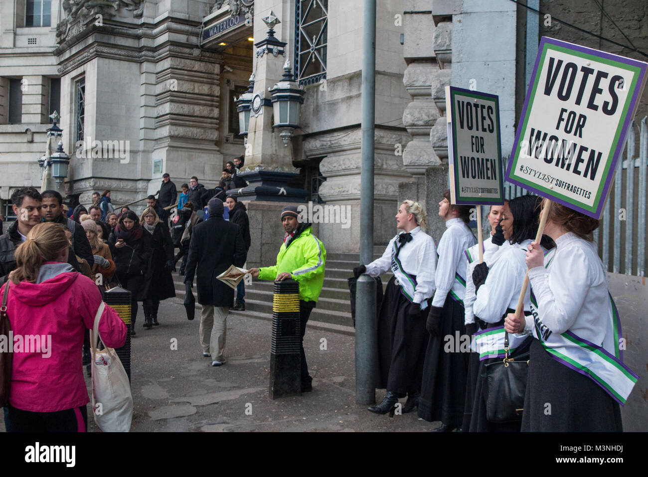 Suffragettes outside Waterloo station in 2018 looking for votes for women through deeds not words - Stock Image