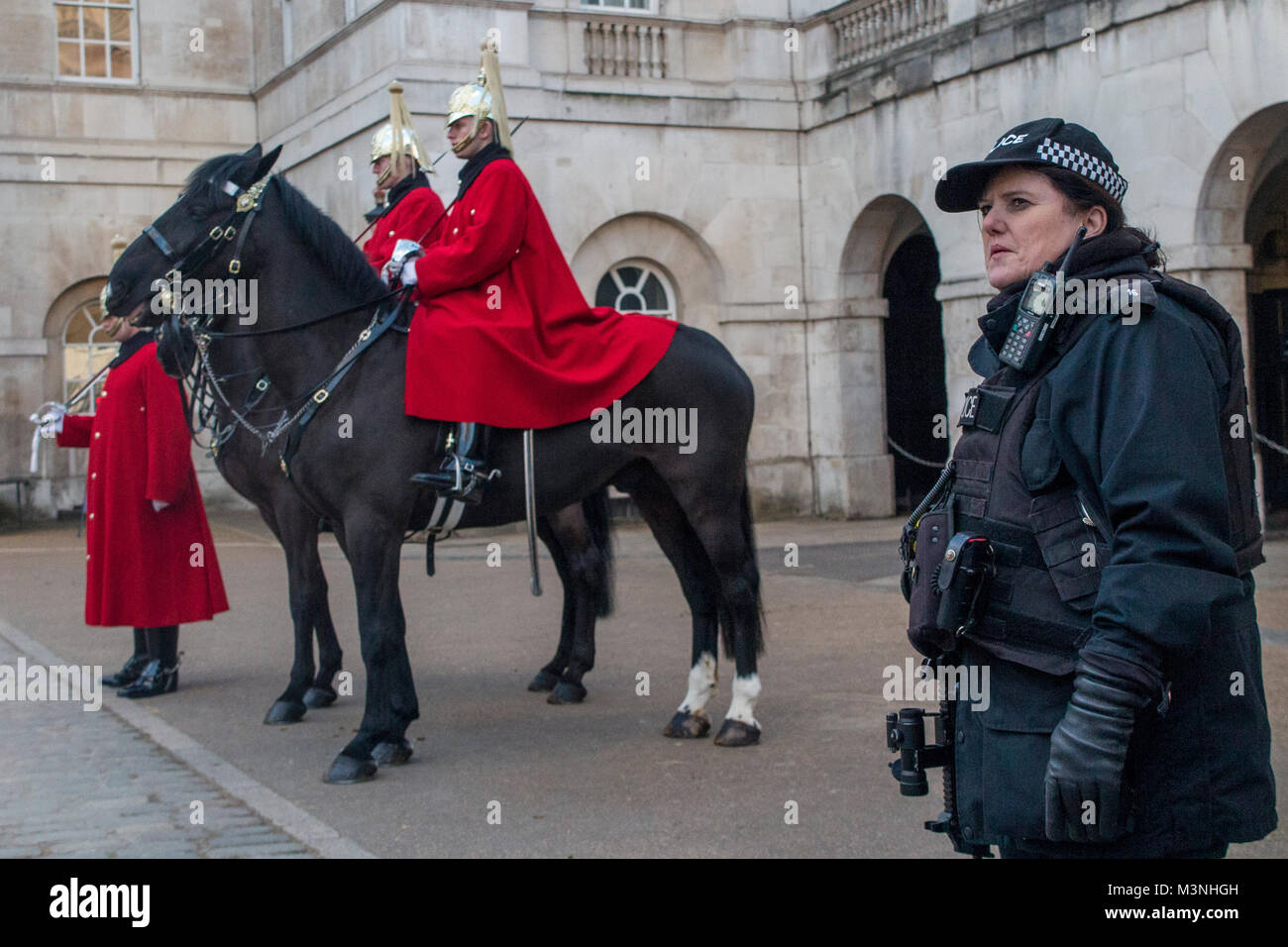 An armed policewoman on patrol with the Horseguards on parade - Stock Image