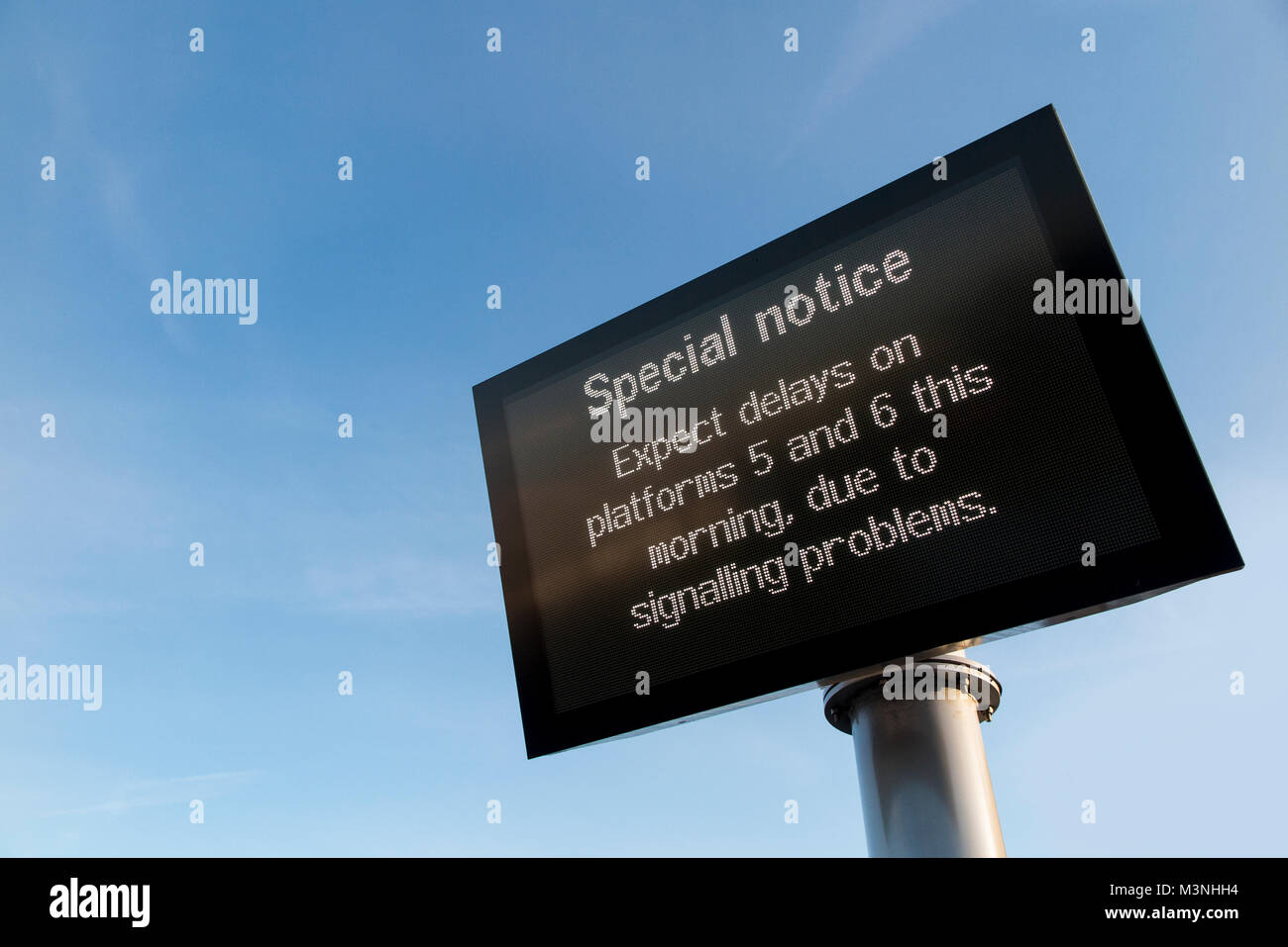 A sign at a railway station advising of delays because of signalling problems - Stock Image