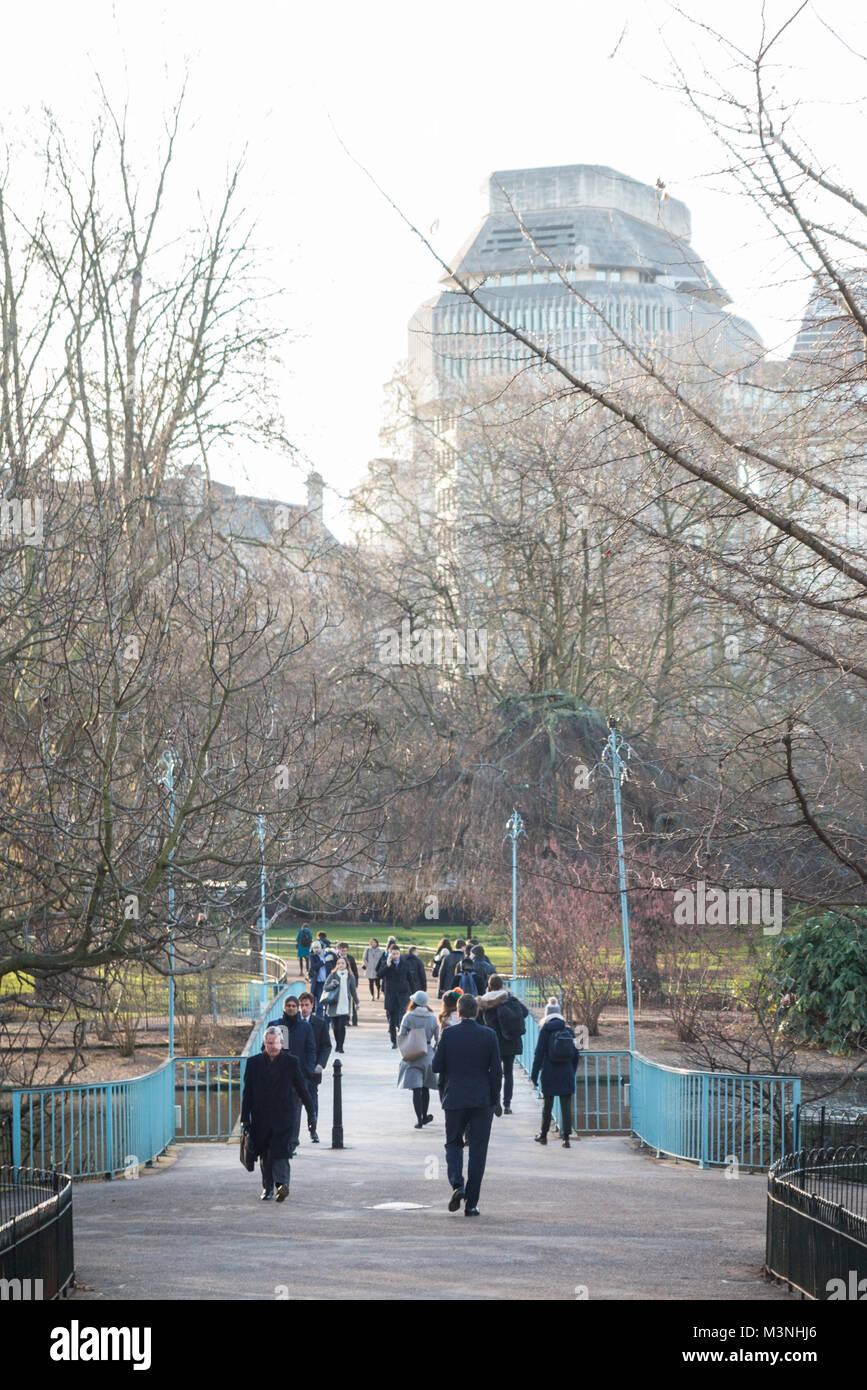 People walking across the bridge in St James Park on their way to work - Stock Image