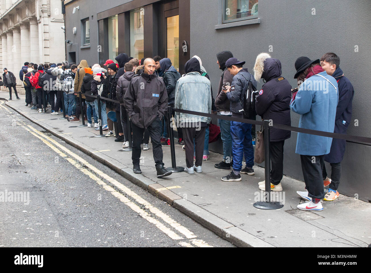 Teenagers queuing for Palace skateboard clothes at a drop at Dover Street Market - Stock Image