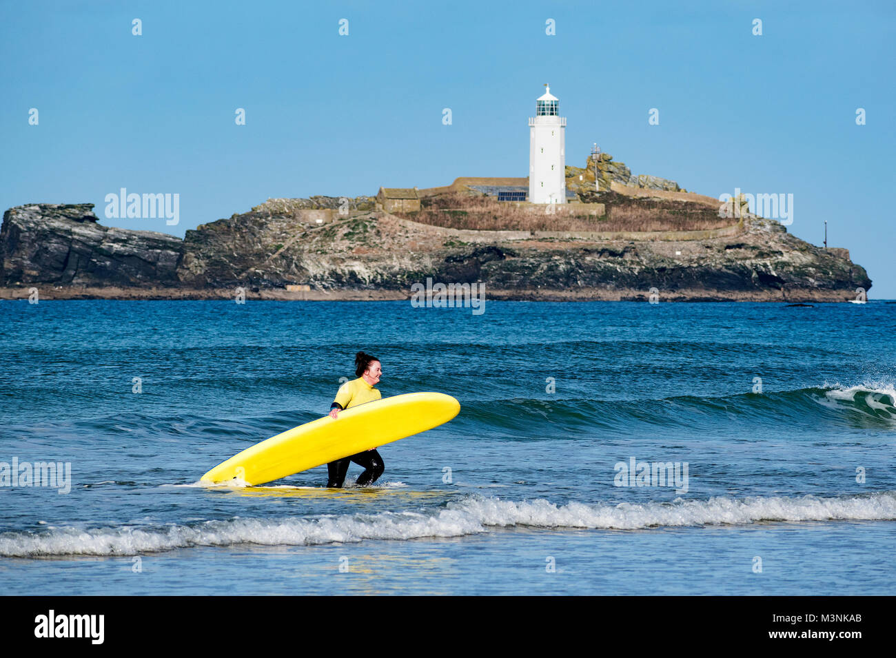 young woman surfer in sea carrying surf board at godrevy, cornwall, england, britain, uk. - Stock Image