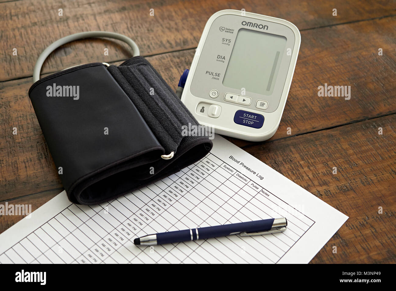 Sphygmomanometer or blood pressure monitor, cuff, and chart ready to monitor heart health.  Concept of healthy lifestyle. - Stock Image