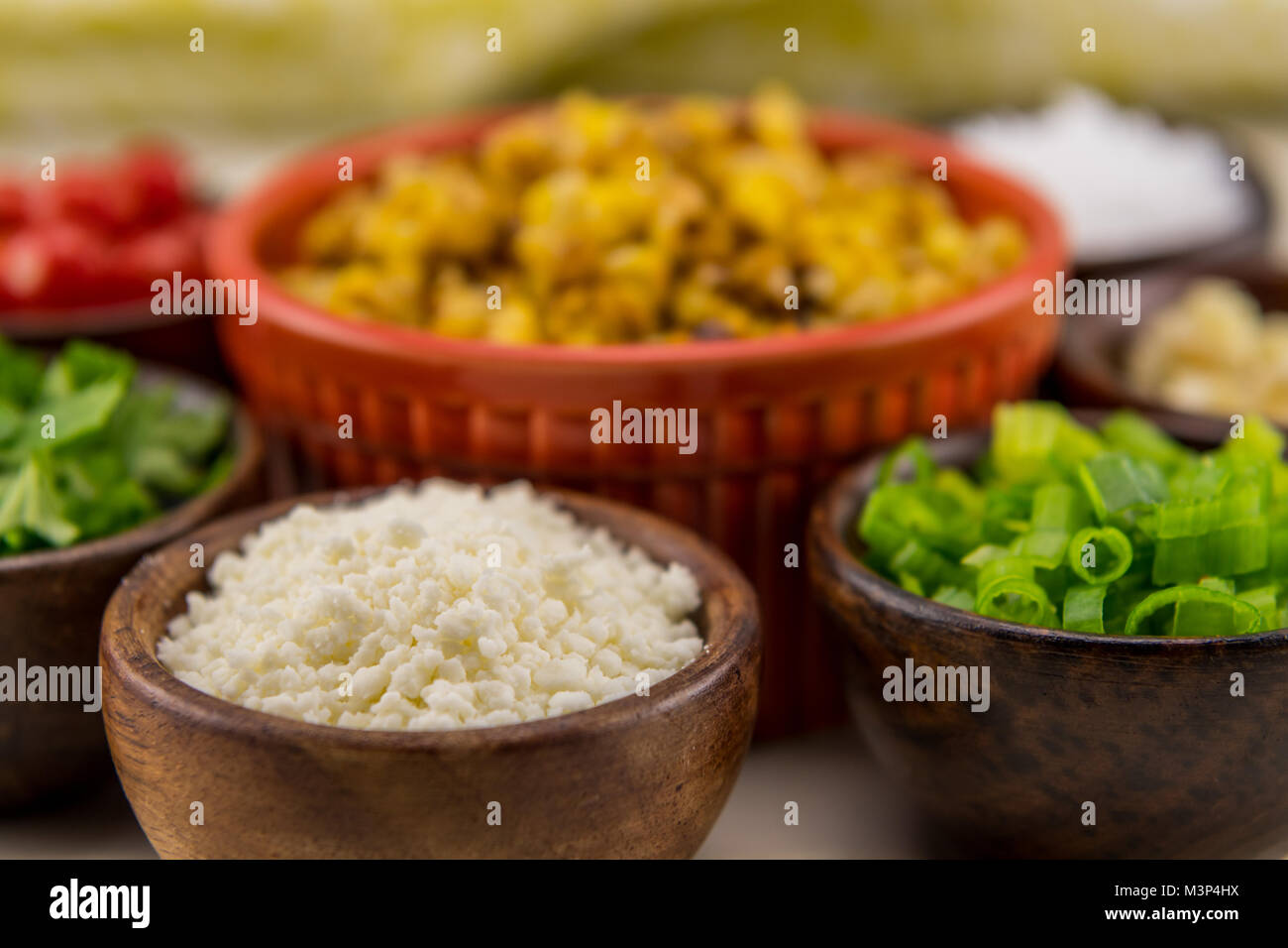 Crumbled Cotija Cheese in Wooden Bowl with other Mexican food ingredients - Stock Image