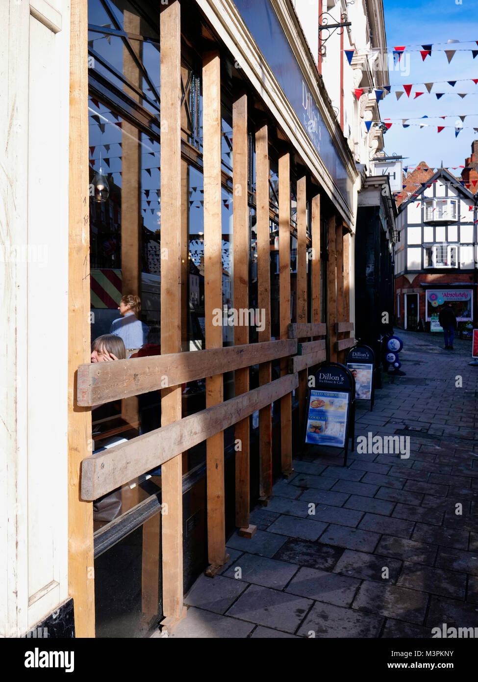 All boarded up. Ashbourne town centre shop windows are boarded up for the start for the Ashbourne Royal Shrovetide - Stock Image