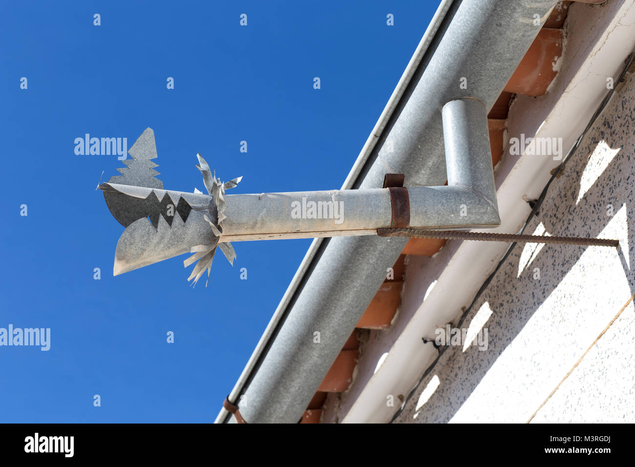 Zinc gutter drainage system dragon shaped over blue sky. Southern spain - Stock Image