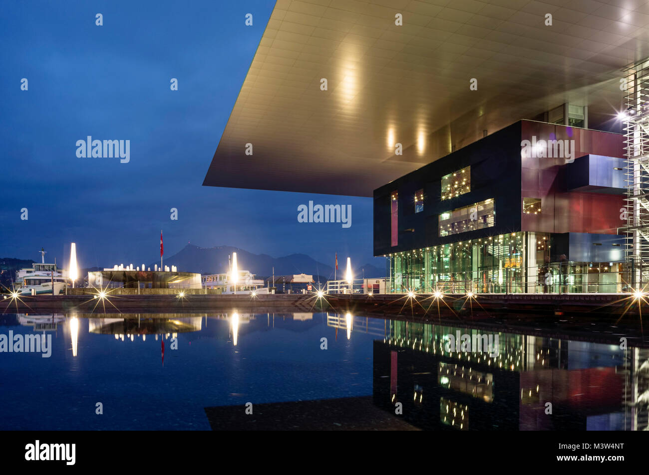 Illuminated fountain and KKL (culture and congress centre of Lucerne) at Europaplatz in the evening, Architect Jean - Stock Image