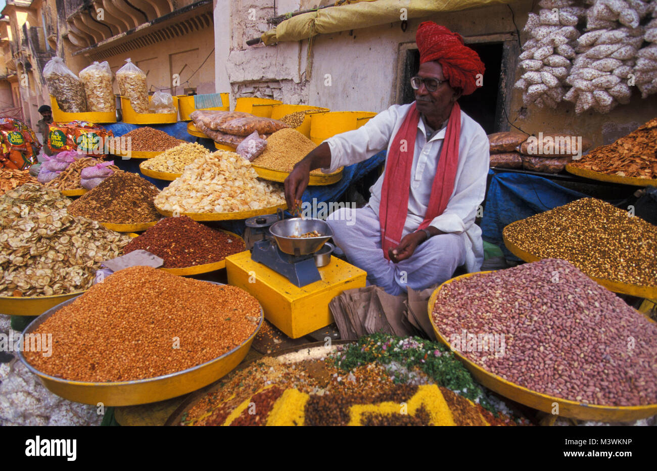 India. Rajasthan. Jaipur. Indian man selling spices on the street near palace. - Stock Image