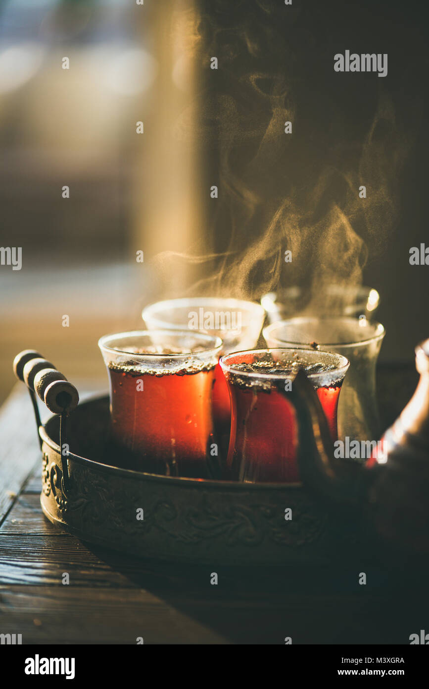 Traditional hot steaming Turkish tea in tulip glasses - Stock Image