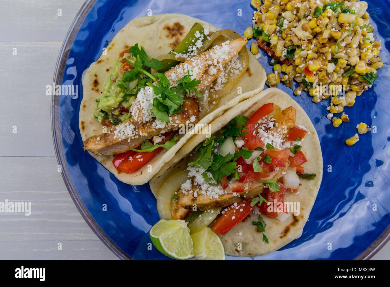Fajitas and Mexican Street Corn on Blue Plate - Stock Image