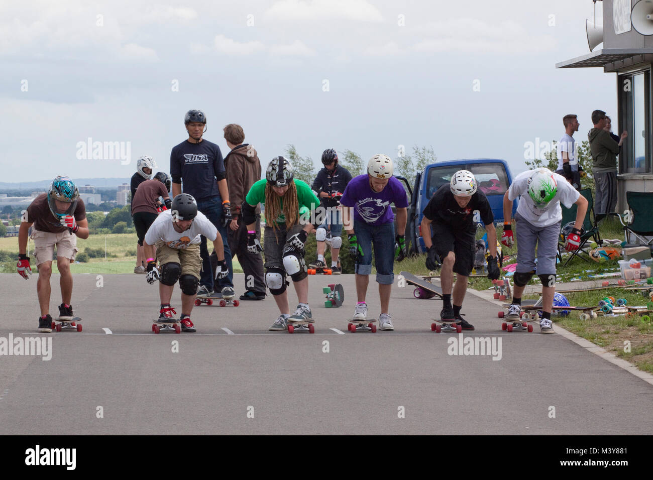 Skateboarders lined up at the start of a downhill race - Stock Image