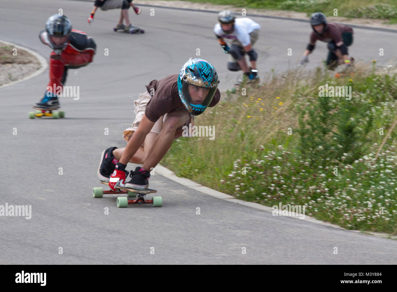 Downhill skateboarders sweep through an S bend - Stock Image