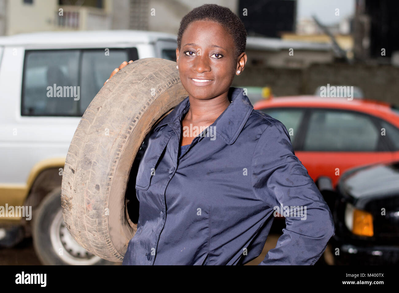 Young mechanic standing and smiling has a tire on her shoulder in her studio. - Stock Image