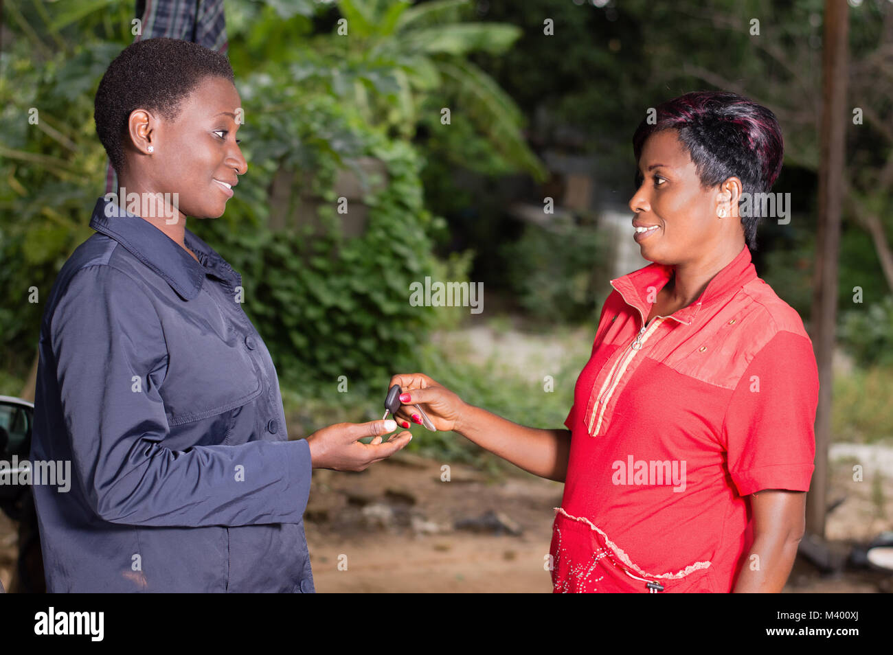 Young woman in red gives the key of her car to the mechanic in a garage. - Stock Image